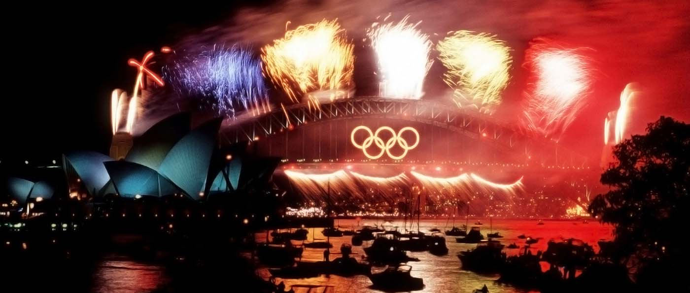 A photo taken at night featuring fireworks on a bridge which has the 5 interlaced Olympic rings centred on the side. The harbour is filled with boats and surrounded by lights in the distance.