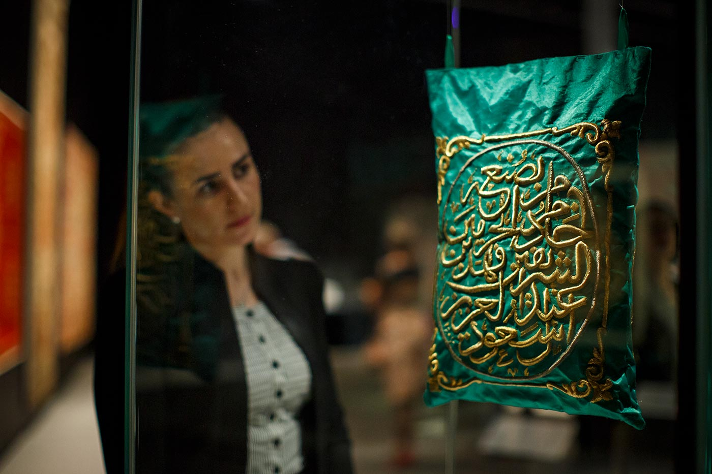 A woman looks at a green and gold object resembling a bag which hangs suspended.