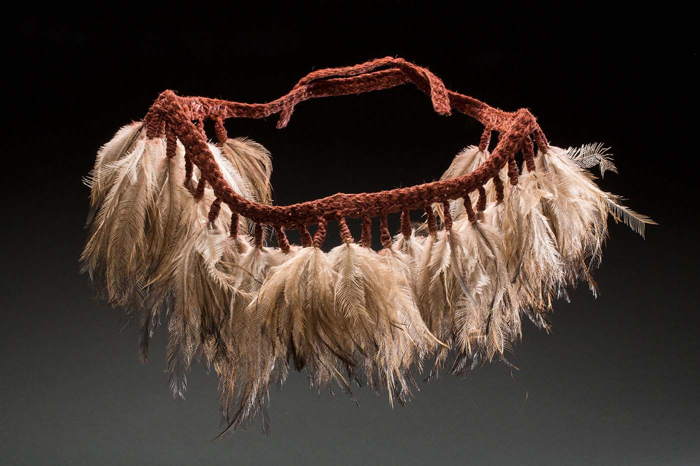 A skirt with a woven fibre belt that is pigmented with a red ochre colour. Every couple of centimetres along the belt hangs a group of emu feathers held in place by woven fibre. There are 34 groups of feathers with some of the woven fibre belt at either end of the skirt so it can be tied on. - click to view larger image
