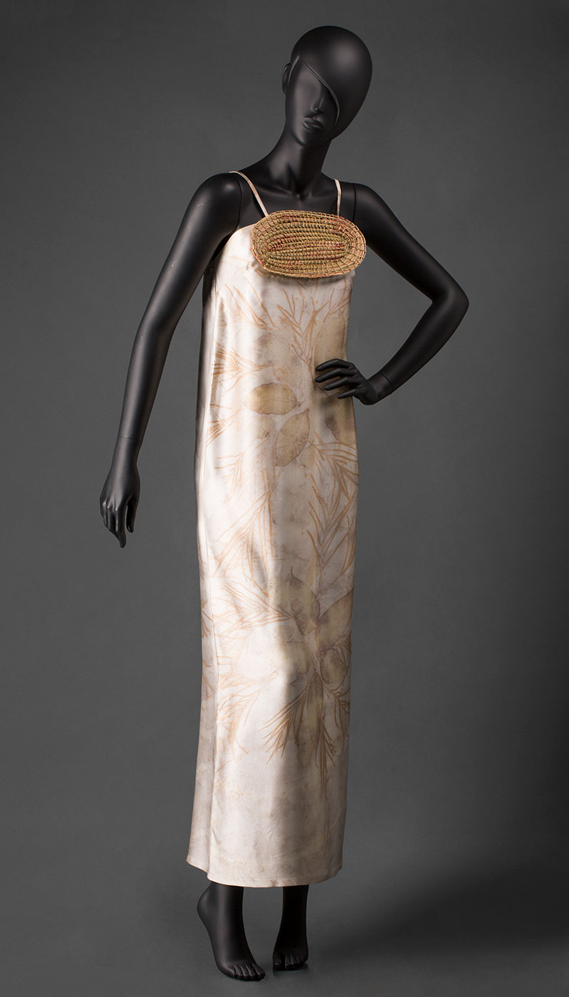 Front view of a mannequin wearing silk dress that is beige in colour with pale brown and yellow leaf designs throughout it. - click to view larger image