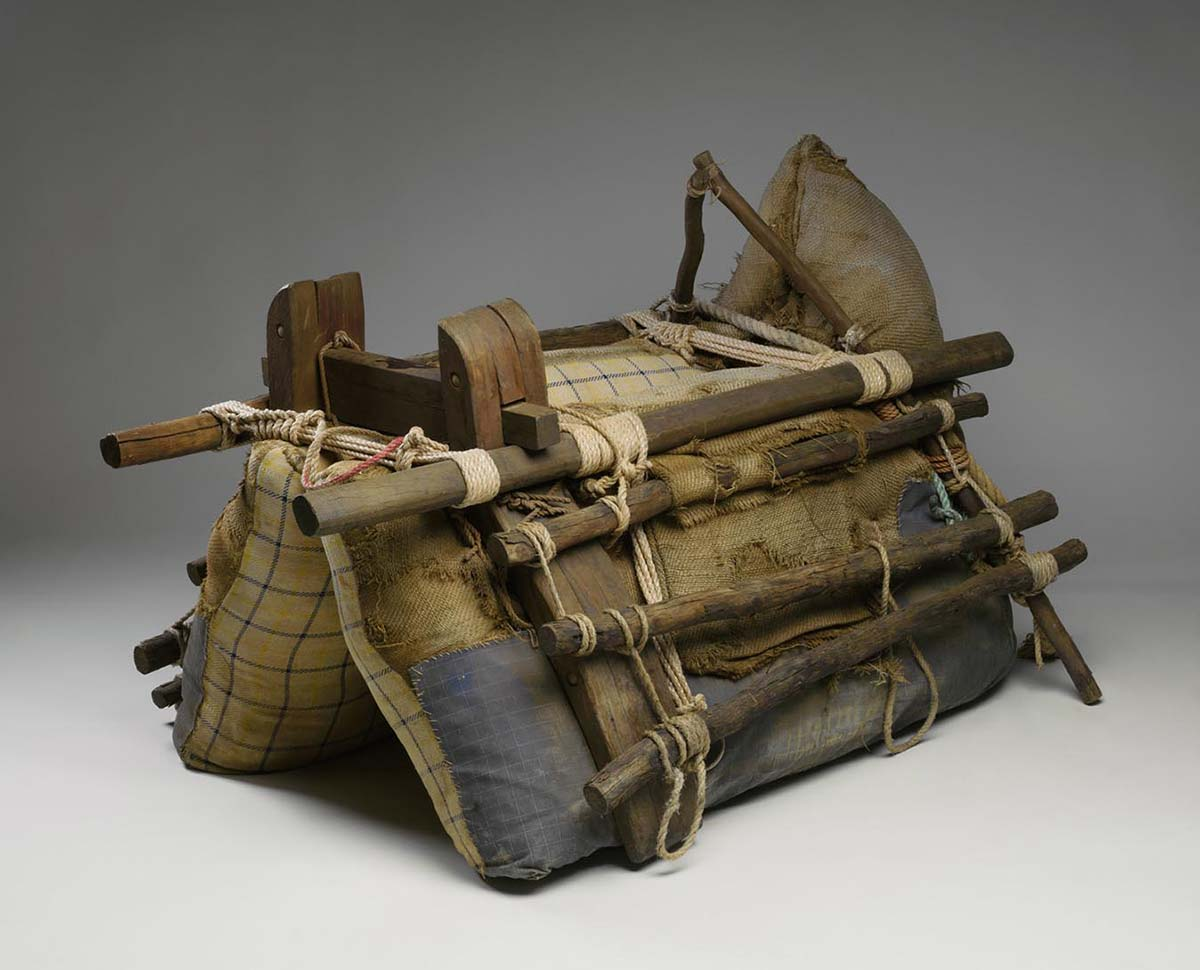 A camel packsaddle with a wooden frame secured with ropes. The wooden frame surrounds padded hessian and cloth bags. - click to view larger image