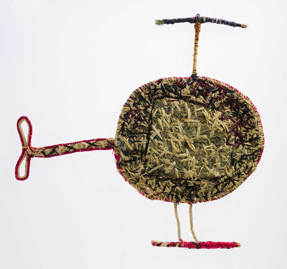 A sculpture depicting a helicopter. The sculpture is made of woven grass and plant material dyed in different colours. - click to view larger image
