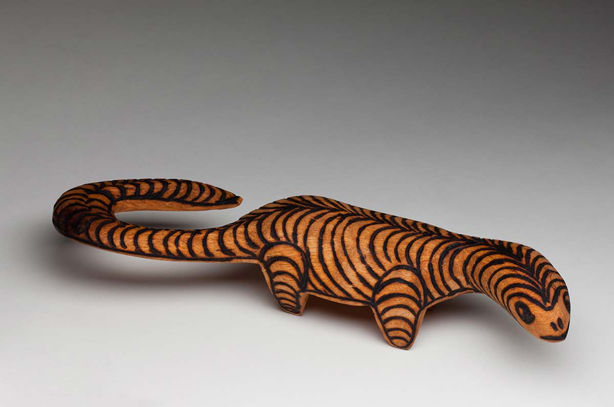 Wooden perente lizard or goanna standing upright on four short legs with its elliptical head turned to the right and a long hooked curled tail. The top exterior is covered with burnt pokerwork designs forming two rows of curving arcs meeting in the centre of the spine while the legs are covered with parallel curved lines. - click to view larger image