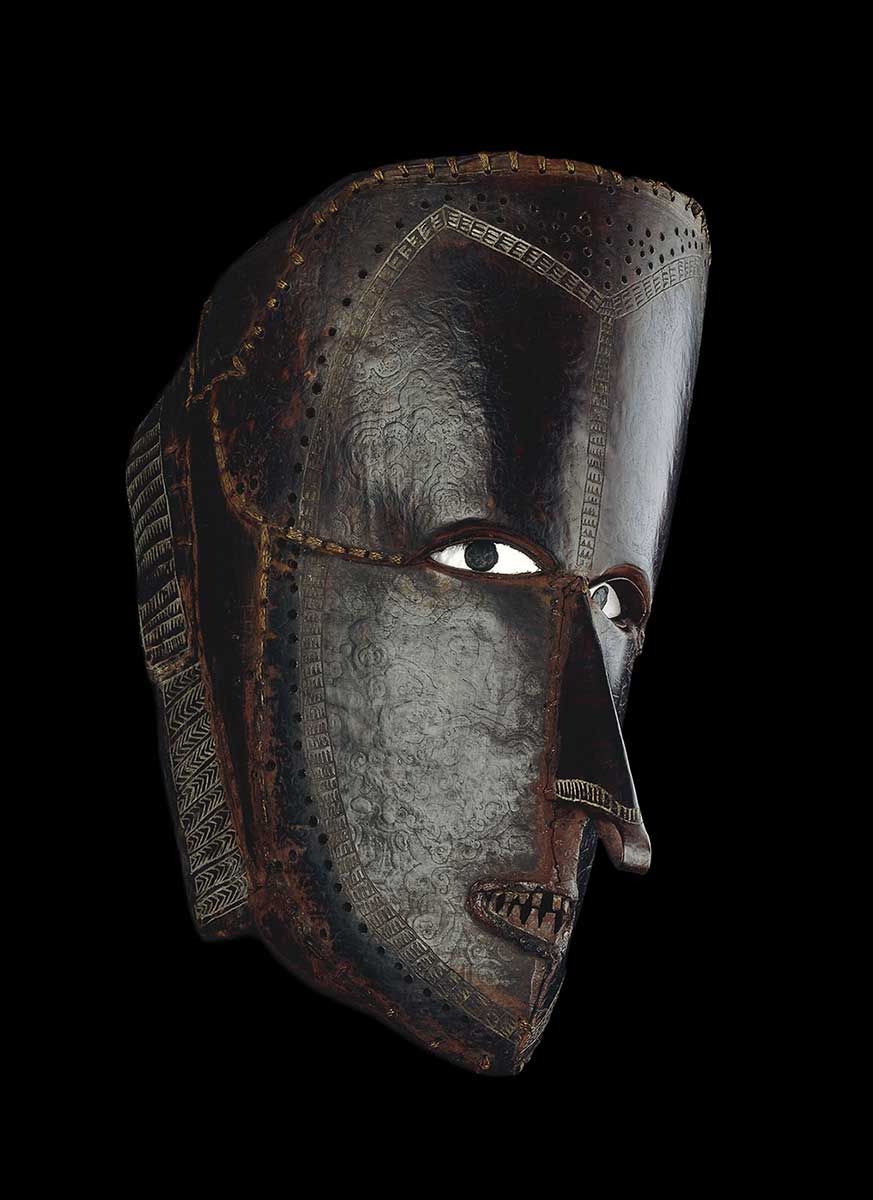 Mask made of tortoise-shell plates which have been bent to form an elaborate human face, and sewn into place with fibre; shell eyes. - click to view larger image