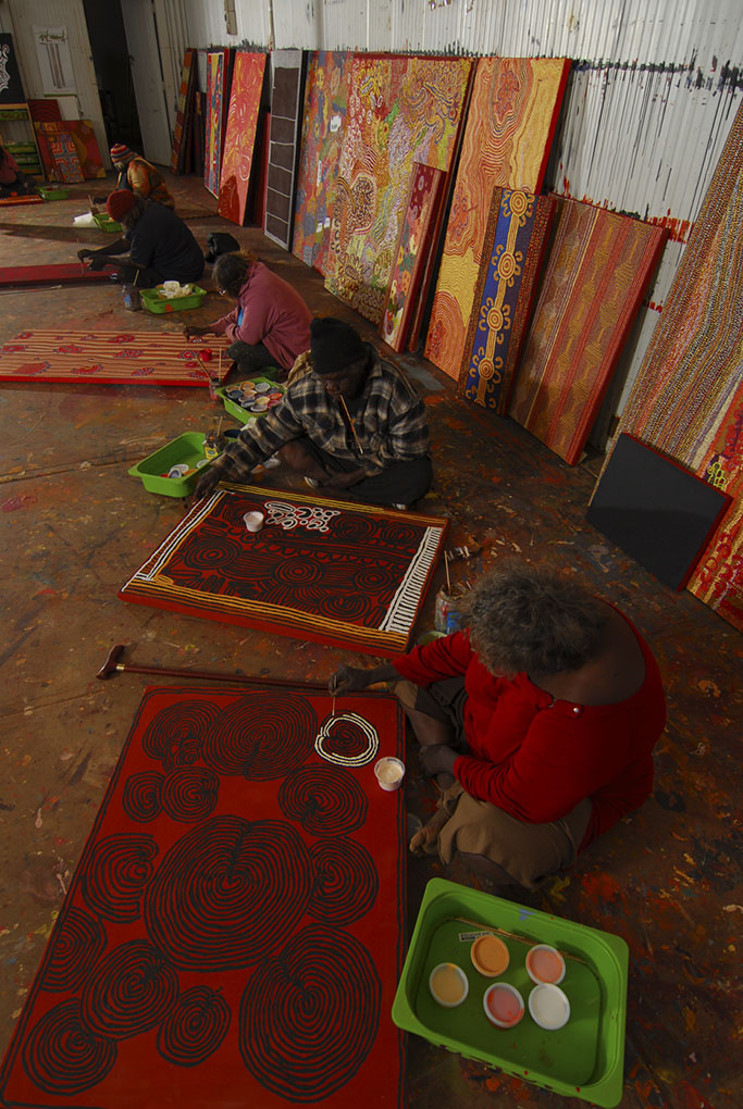 Colour photograph showing five seated Aboriginal artists working on individual paintings. Various other paintings line the rear wall. - click to view larger image