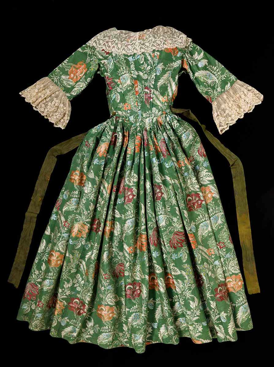 The back of a green and floral dress with lace trim on the sleeves and collar with a long green sash like belt stitched at the waist. - click to view larger image