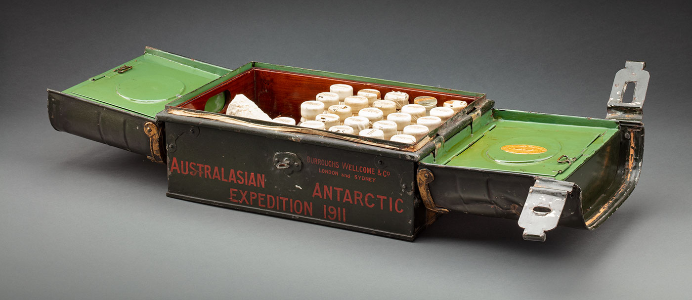 Open metal box containing glass bottles of medicine. Painting on the side of the chest are the words, 'Australasian Antarctic Expedition 1911'.