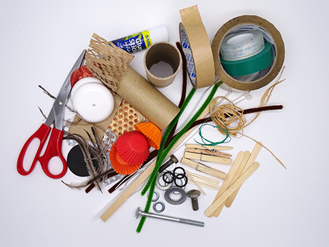 A range of objects including: cardboard tubes, toothpicks, sticky tape, bottle tops, pipe-cleaners, coloured paper, glue, pencils and textas.