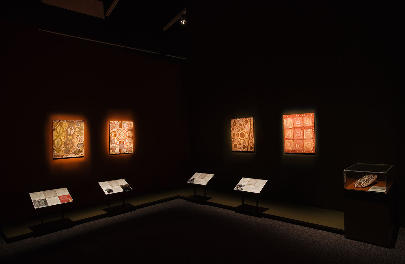 Gallery shot showing four Papunya canvases, including 'Possum Men of Yirtjurunya' at far right. - click to view larger image
