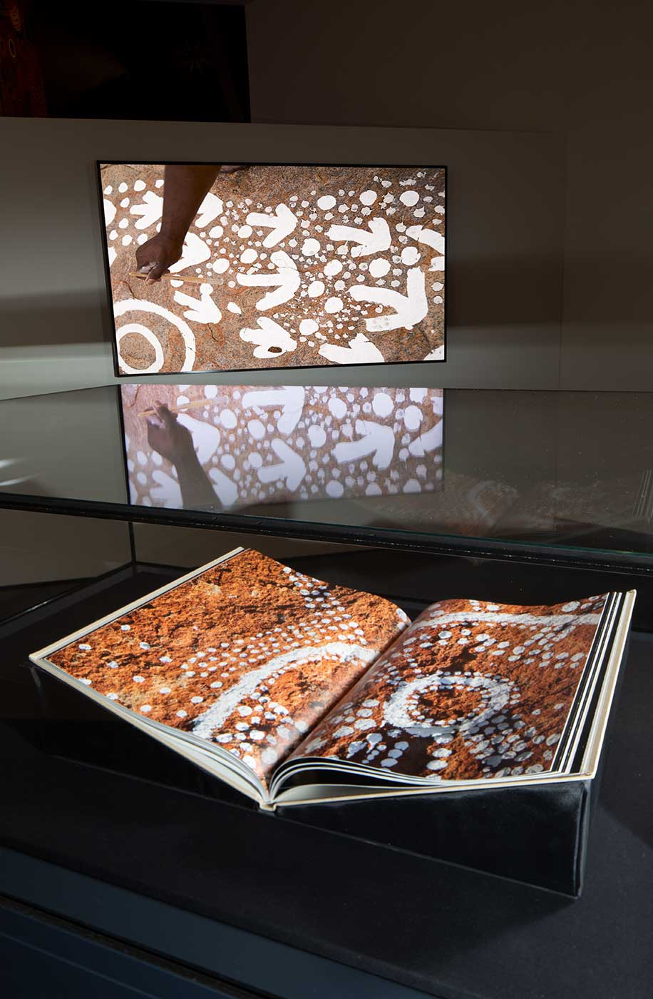 An image of a book open at a picture of indigenous artwork. - click to view larger image