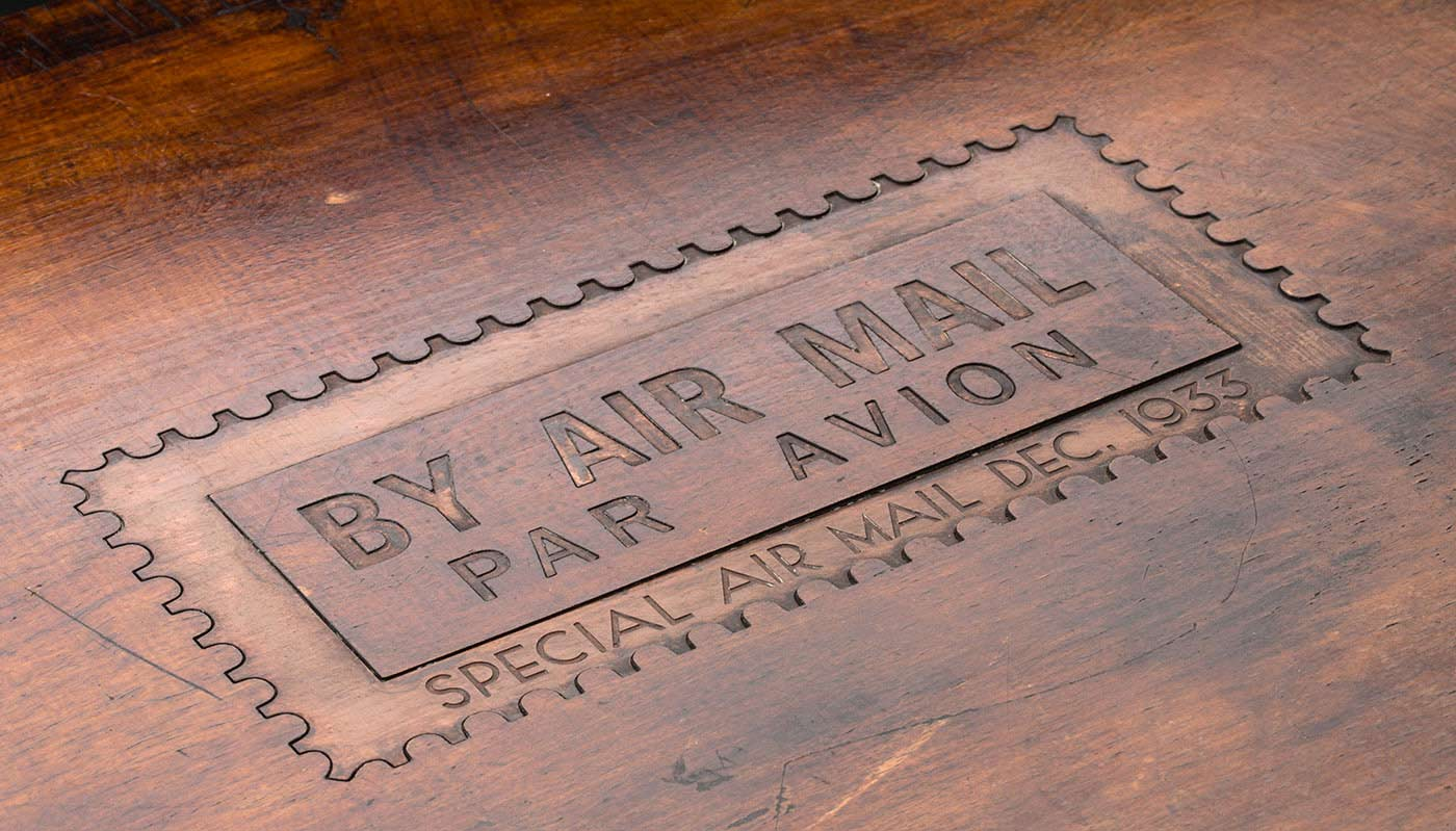 A wooden box with a hinged lid and tooled leather interior. The exterior of the box lid is engraved with 'BY AIR MAIL /PAR AVION / SPECIAL AIR MAIL DEC 1933'. In the lower interior section of the box there is a metal cavity designed to house commemorative flight covers. This has a metal border with a stamped design featuring the words: 'BY AIR MAIL / PAR AVION'. An engraved metal plate is attached to the interior underside of the box lid and reads: 'TO THE MOST VIRTUOUS OF MEN / VIA