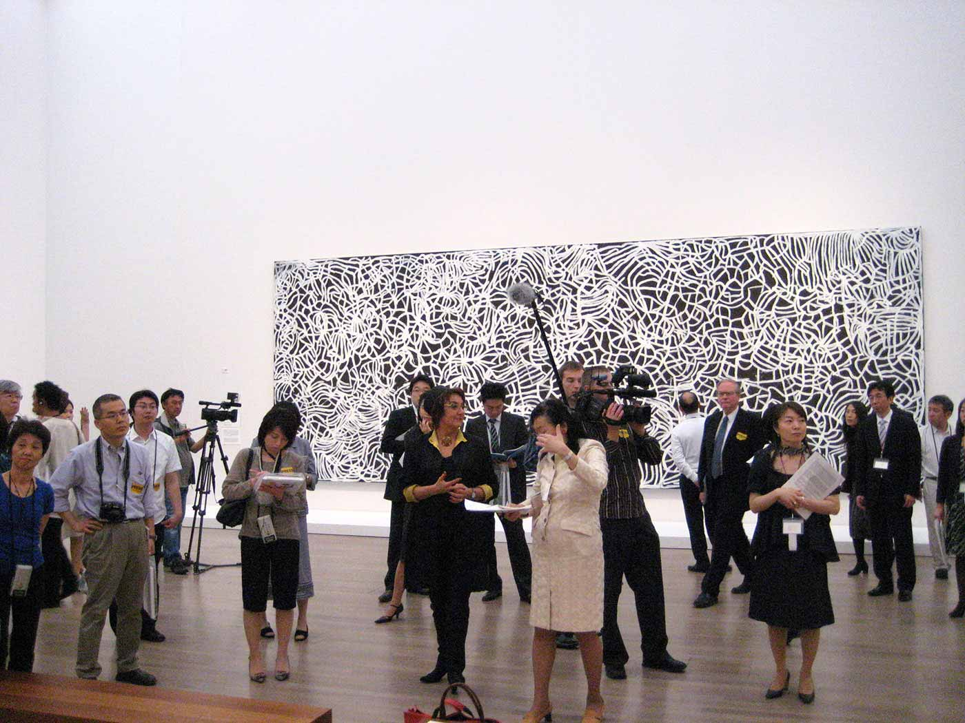 Media standing in an exhibition space with a large painting in the background. - click to view larger image