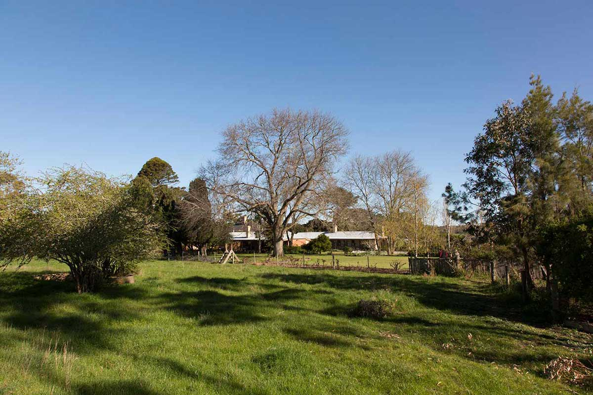 Country setting featuring a house with a tin roof surrounded by grass, trees and garden.