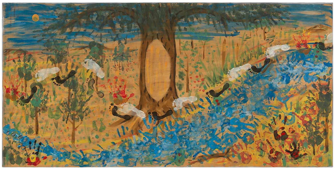 A painting on board featuring a blue river or stream, a blue sky, and a tree surrounded by other smaller trees and foliage. Merging within the landscape are hand and feet prints made of paint.