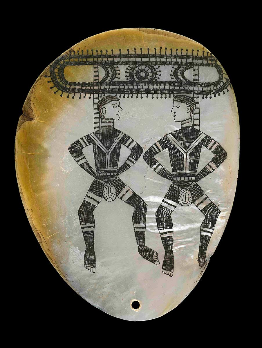 Ornament and pubic cover made from carved and polished pearlshell. The shell has been polished and incised with two figures, both wearing pearlshell.