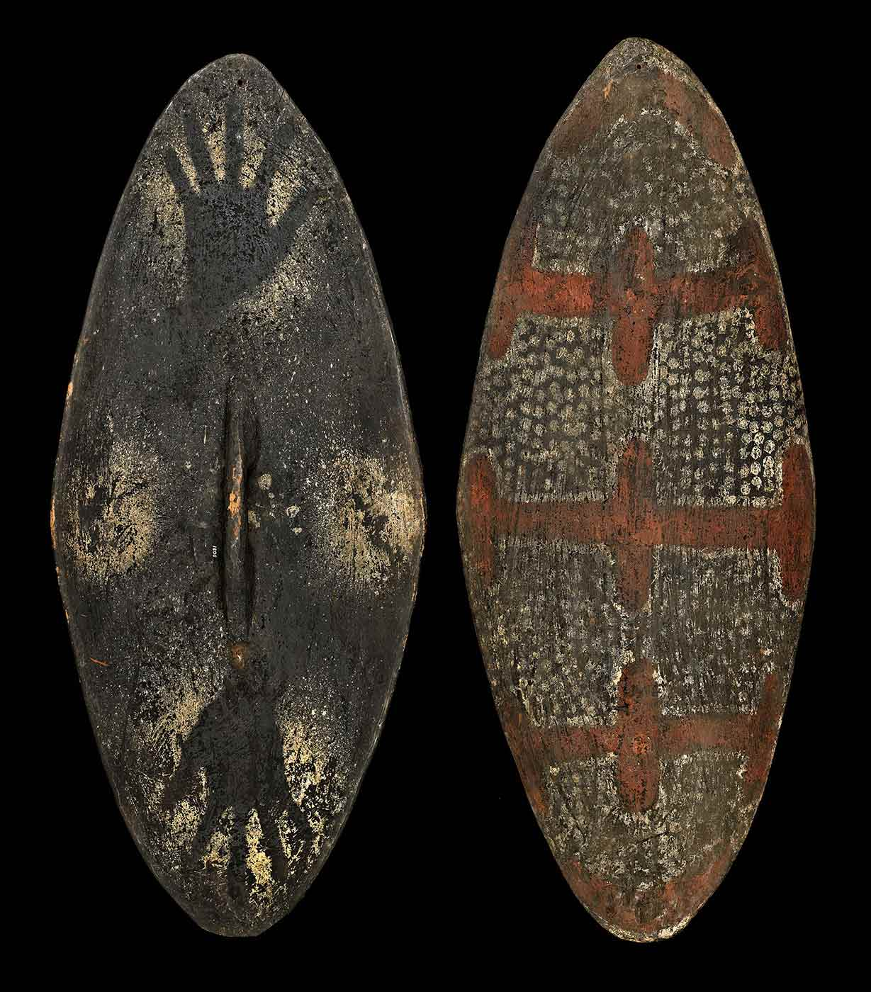 Large oval shaped wooden shield, painted with broad red bars with white spots on a black background. The reverse side features a handle and sprinklings of white paint as well as two hand stencils.