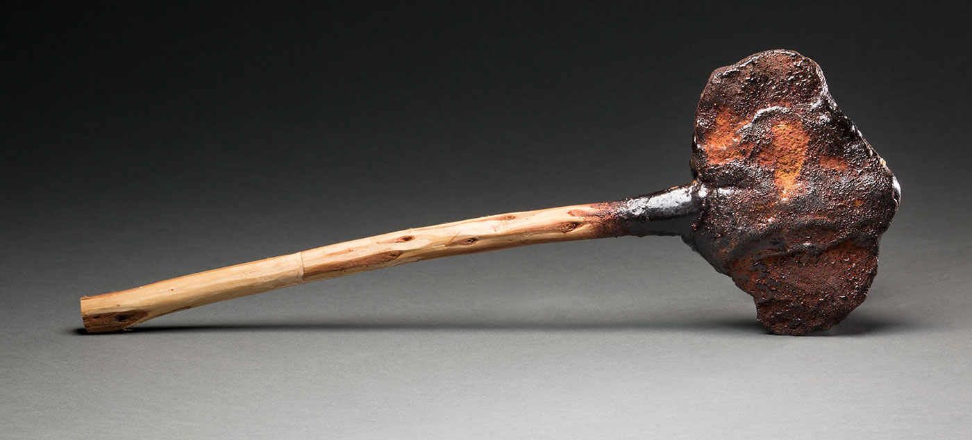 Wooden-handled axe with stone blades adhered with resin.