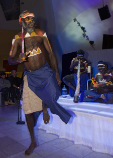 A colour photograph of an Indigenous man engaged in a traditional dance. He wears a sarong-style garment around his lower body and has traditional patterned markings on his upper body. Behind him on a low stage sit two other Indigenous Australian men. One playing the didgeridoo while the other plays a pair of clapping sticks. Both have traditional markings on their upper bodies.