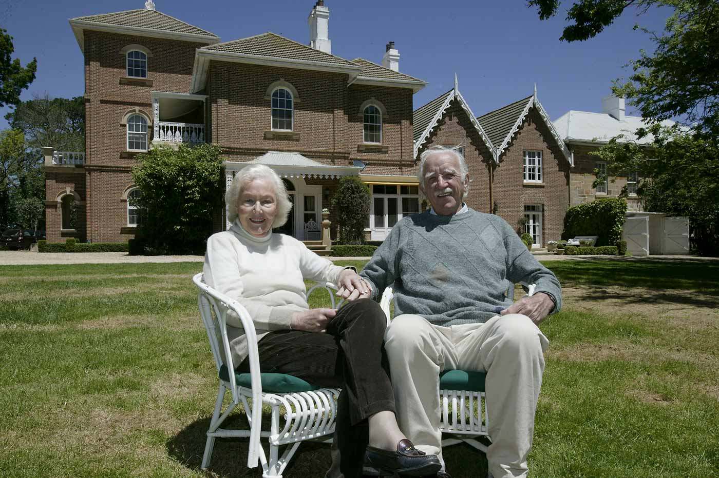 Pamela and Jim Maple-Brown seated on wooden chairs on the grass in front of the main Springfield homestead.