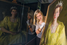 Curator Laura Breen, wearing white gloves, peers around a framed portrait of Queen Elizabeth II. The scene is reflected in a window at the left of the image.
