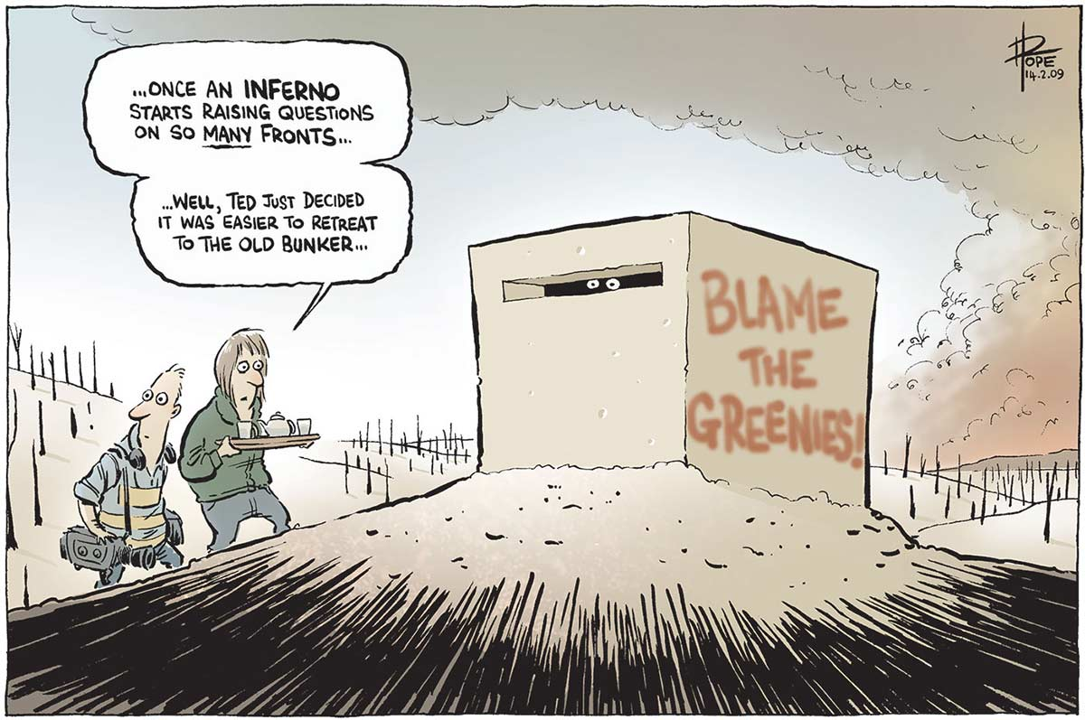 A colour cartoon depicting a pair of eyes peeping out a small slot at the front of a bunker with 'Blame the Greenies' spray-painted on the side. Smoke rises in the distance and the surrounding countryside is burnt out, with bare tree trunks all around. A camera man and a woman carrying a refreshments tray creep towards the bunker. The woman says, 'Once an inferno starts raising questions on so MANY fronts ... Well, Ted just decided it was easier to retreat to the old bunker'. - click to view larger image