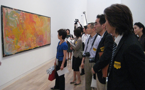 A painting in pastel colours of yellows, pinks, blues and greens displayed in landscape orientation is on the left side of the image; nine Japanese viewers range along the right side of the image. One of the viewers in the background of the image holds a camera above their head.