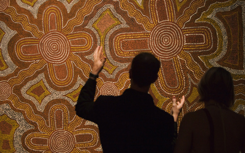 This image is shot from behind with two people viewing an Aboriginal dot painting in ochre colours. All of the light in the image is on the painting; both people are in silhouette with only their outlines visible, except that the man who is on the left is gesturing towards the painting and his hands are in the light.