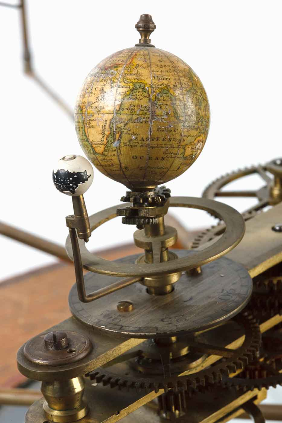 Cropped image of a contraption featuring a globe fixed to brass cogs and other various mechanical pieces. - click to view larger image
