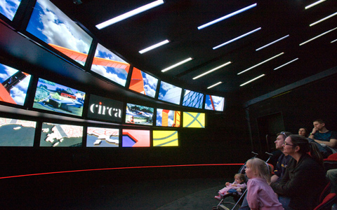Seven people sit in a darkened room in the front seats of a theatre. There are 18 screens ranged in three rows with a variety of images and a series of slanted light areas on the ceiling. On the centre screen is the word 'circa' in white text on a black background.