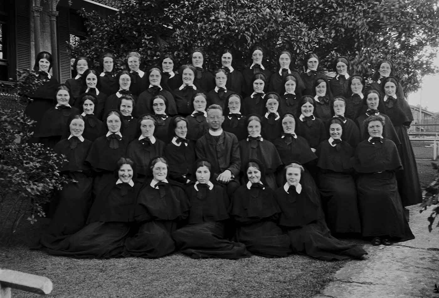 Black and white group portrait of women wearing a uniform of black gowns with white dresses. A priest sits in the centre towards the front.