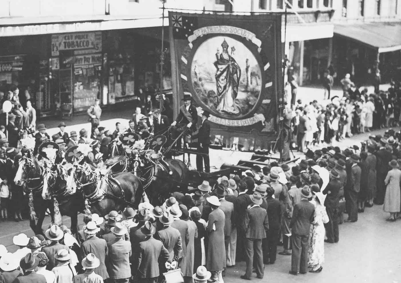 Black and white photo of a procession down a city street featuring a horse drawn float with a large banner, while crowds look on. - click to view larger image