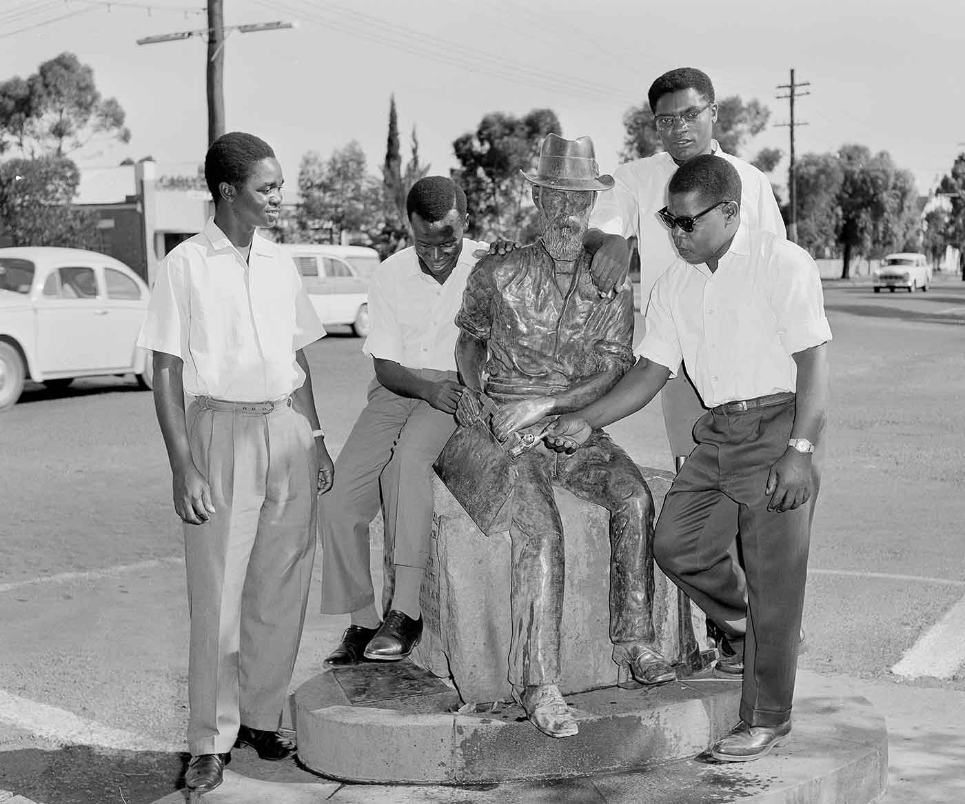 Black and white photo of a street scene with four men standing and sitting around a memorial statue of a man.