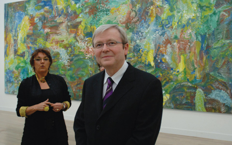 Kevin Rudd is at the centre-front of the image facing the camera. To the left of the image and further back stands curator Margo Neale. In the background is a large painting in greens and blues with yellow highlights.