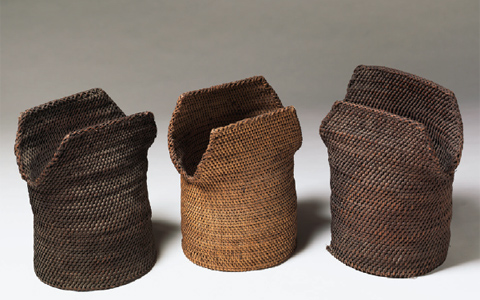 An image of three basket-type body armour objects. The lower part of the one-piece armour is tube shaped. Front and back flaps stick up from the tube to protect the top of the chest while allowing the arms and shoulders to move freely.
