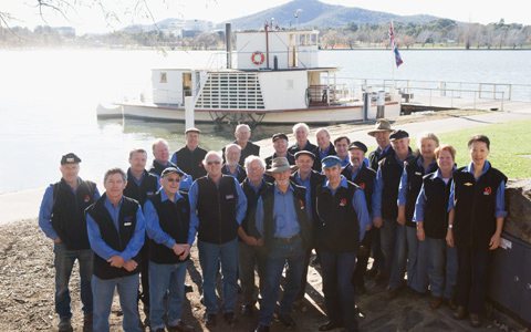 Group of 23 people standing in front of the paddle steamer at its dock. The lake and hills can be seen in the background.