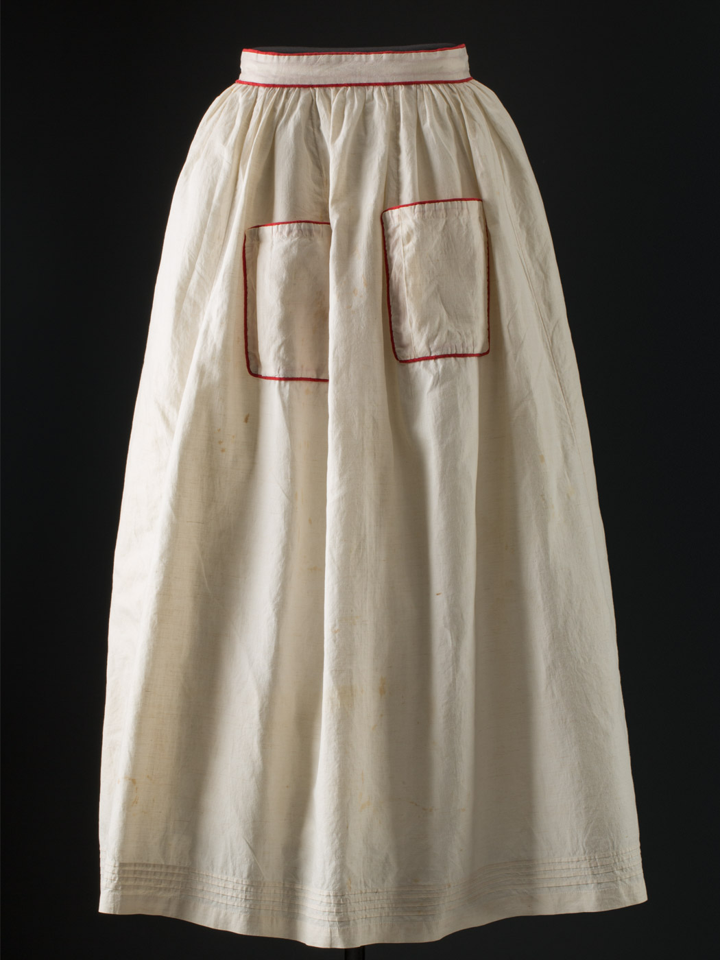 Front view of a white apron with red piping. - click to view larger image