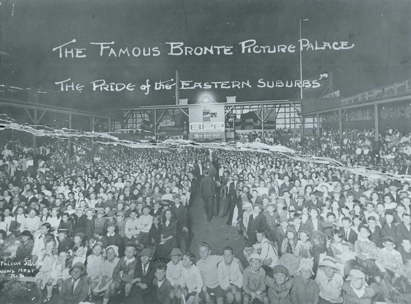 Black and white photo of a large crowd of people in an open air cinema with hand written text 'THE FAMOUS BRONTE PICTURE PALACE THE PRIDE OF THE EASTERN SUBURBS',