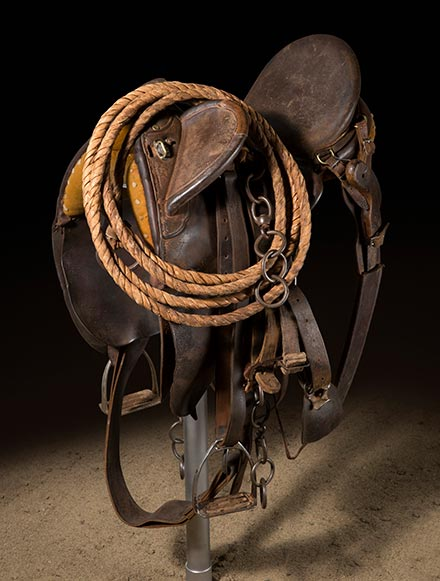 A dark brown leather saddle mounted on a pole.  - click to view larger image