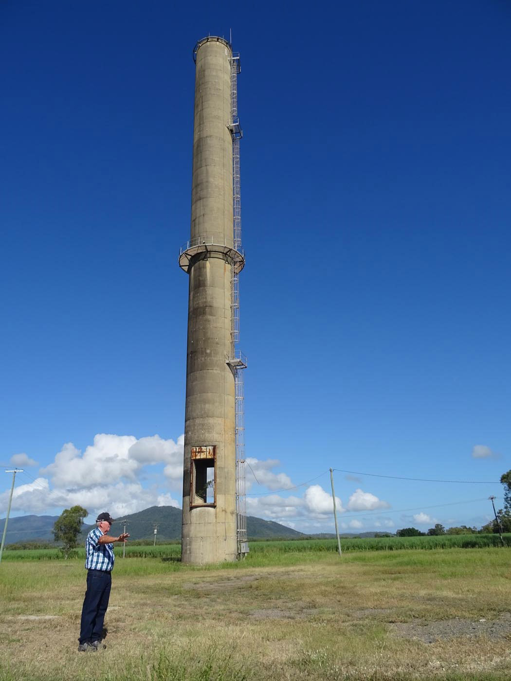 A colour photo of a man pointing, in front of a tall cement tower. - click to view larger image