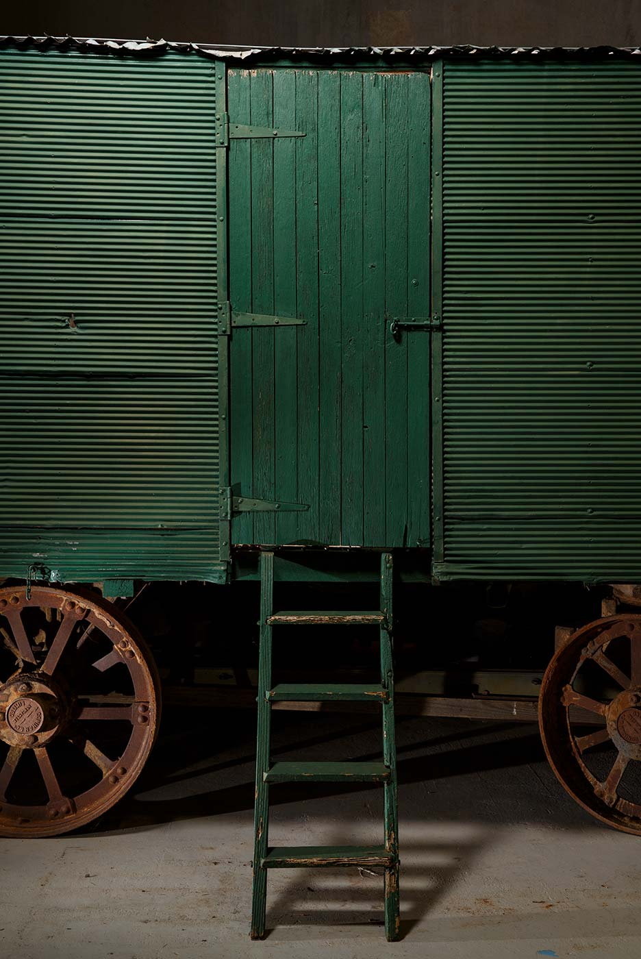A cook's galley in the form of a metal-clad, timber and iron-framed box raised on wagon wheels. This view is of one of the galley's side doors closed. - click to view larger image