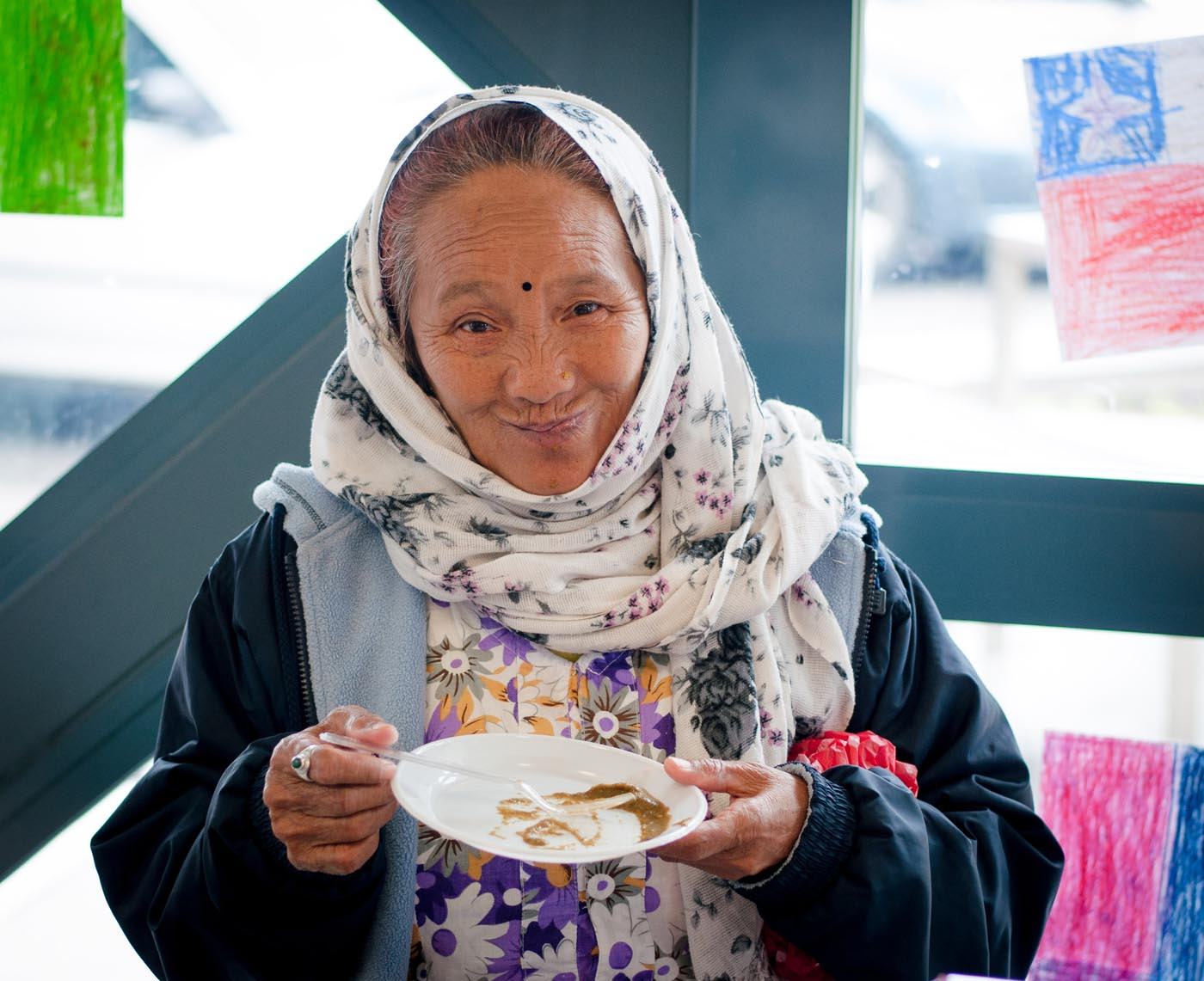 Photo of an elderly lady holding an empty lunch plate - click to view larger image