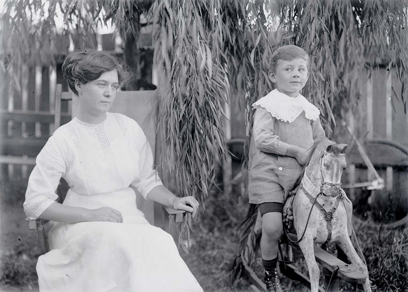 A photographic glass plate negative showing a woman sitting in a chair beside a boy riding a toy rocking horse. There is a bicycle and picket fence visible in the background. - click to view larger image
