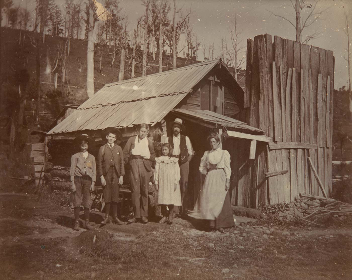 A black and white family phoograph in front of a small wooden house/ hut at the base of a slight hill dotted with leafless tall trees. In the image, there are three young boys standing on the left, a young girl in the centre just in front of the father figure, and finally on the right is the mother figure leaning against the hut. The tallest of the young boys standing near the centre of the shot, is wearing a sling around his left arm. This photograph has been developed for Plate 2 in Box 9 and is the same as photo 9 only in focus and photo 10. - click to view larger image