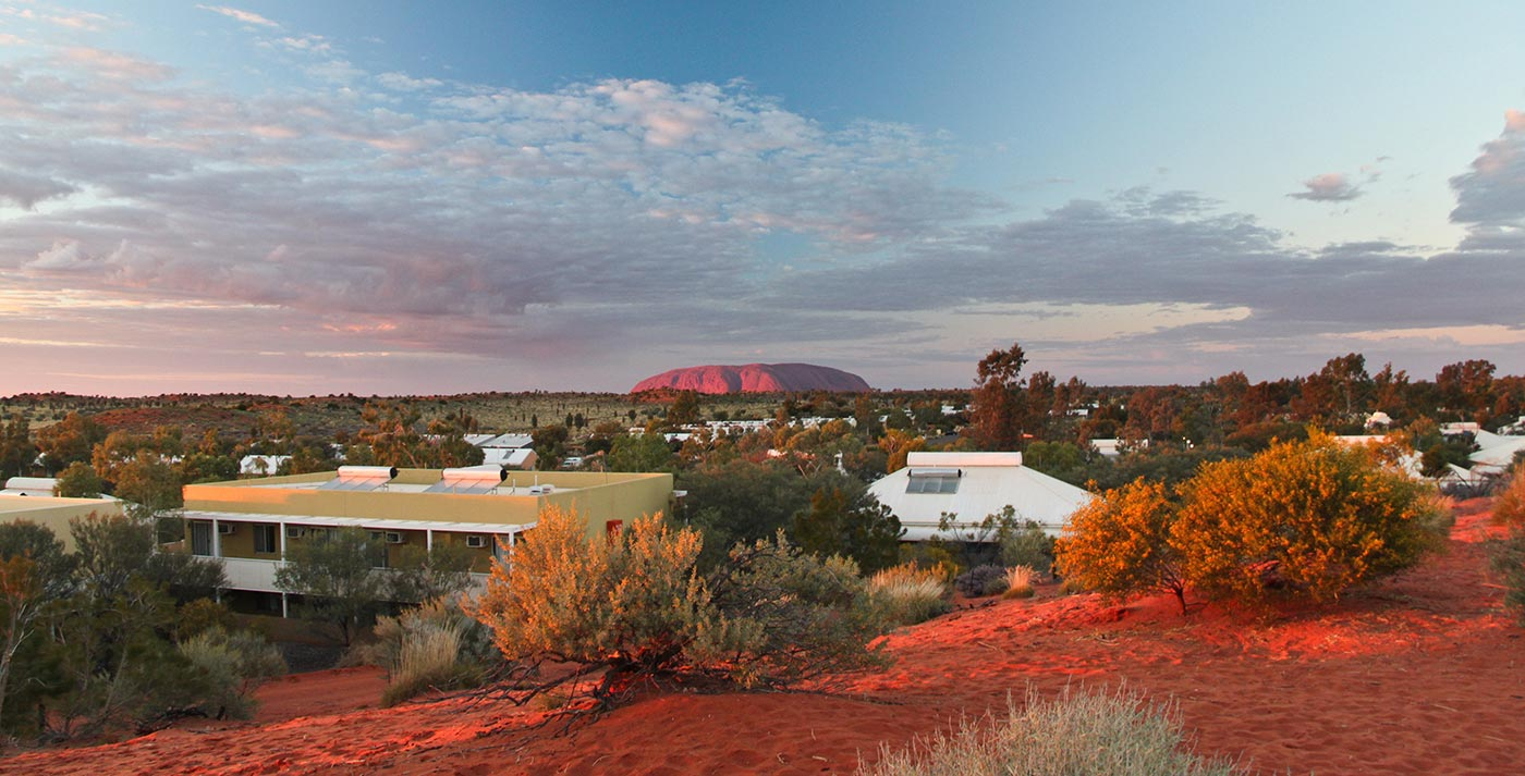 Sunset at Yulara tourist village, with the massive stone mountain Uluru, or Ayers Rock, rising in the distance, July 2011