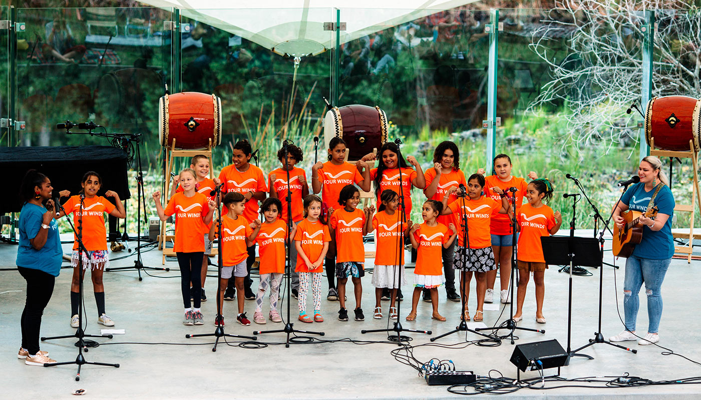 A group of children and adults, wearing orange t-shirts marked with the words 'Four Winds', perform on stage.