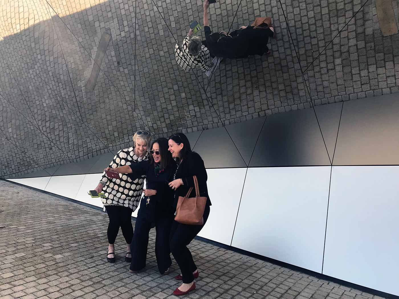 Three women taking a selfie in front of a large mirror wall. - click to view larger image