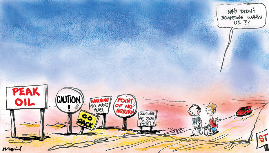 A man and a woman, facing the viewer, walk up a long, dusty road somewhere in the outback, both carrying petrol containers. Their car is parked further down the road with its hood up. In the foreground of the cartoon a series of six signs of different sizes and shapes, that they must have driven past, say, 'Peak oil', Caution!', 'Go back', 'Warning No more fuel', ' Point of no return', 'Continue' at your own peril!' The speech bubble above the woman's head says, 'Why didn't someone warn us?!' - click to view larger image