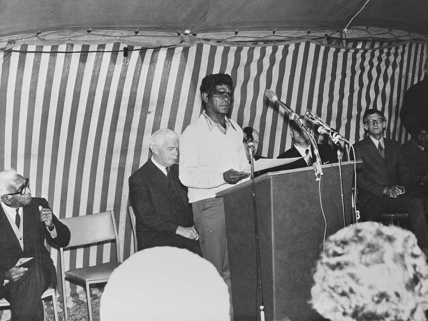 Black and white photo of a man standing at a podium and speaking to an audience. There are several other male officials sitting behind him.