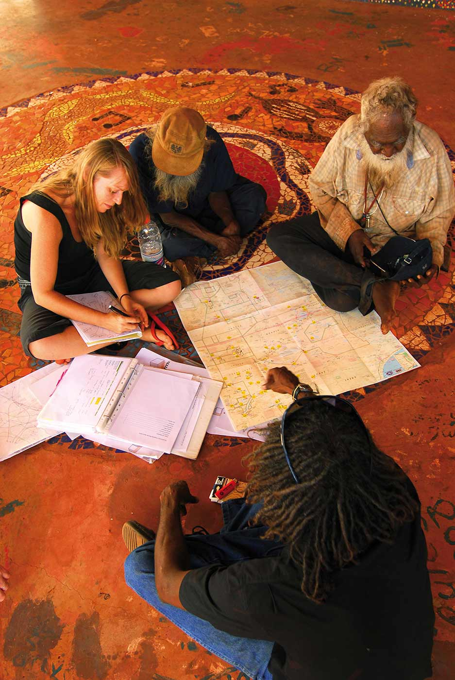 Colour photo of a group of people sitting on the ground in discussion over maps and paperwork.