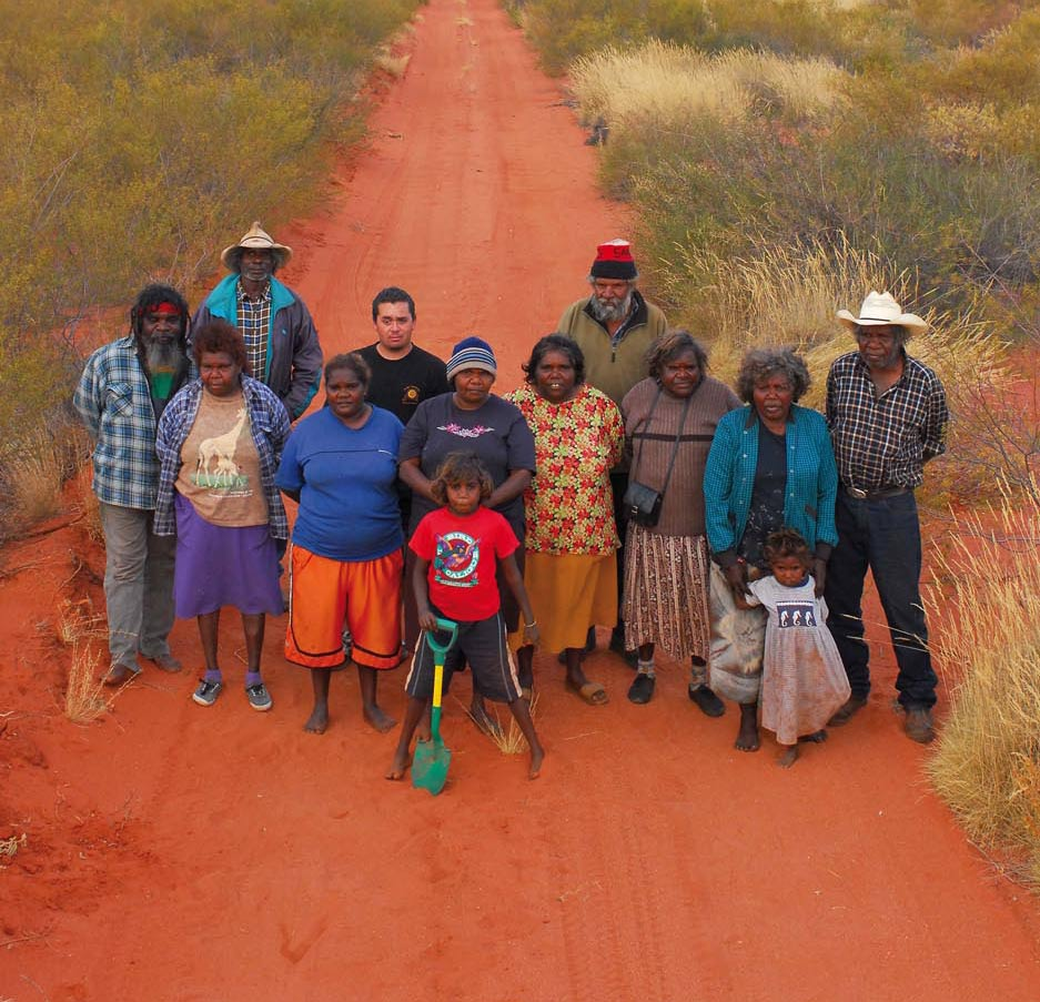 Group portrait of people standing on a red sand track.